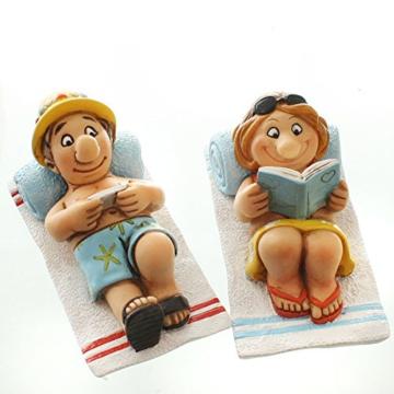 Witziges Urlauberpaar auf Strandtuch mit Buch und Tablett -